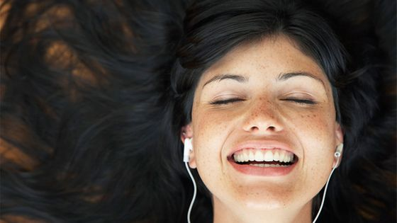 Young woman listening to earbuds with hair spread out © Tomas Rodriguez/Corbis