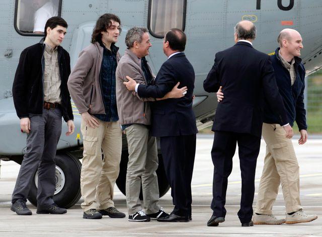 Les otages lors de leur retour en France accueillis par Fabius et Hollande