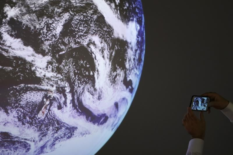 Un participant prend une photo de la réplique d'une planète durant la COP 21