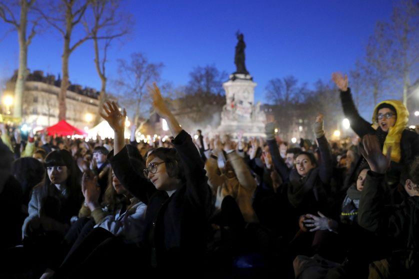 Les participant-e-s à l'AG lèvent les mains et les agitent, en aprobation