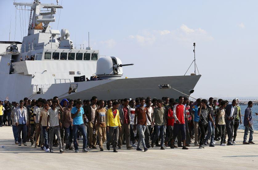 Des migrants africains débarquent d'un vaisseau italien dans le port d'Augusta