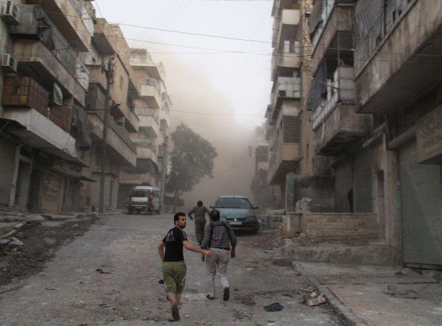 A Alep, des civils dans les ruines d'un marché dans le quartier d'al Ma'adi, en juillet 2015