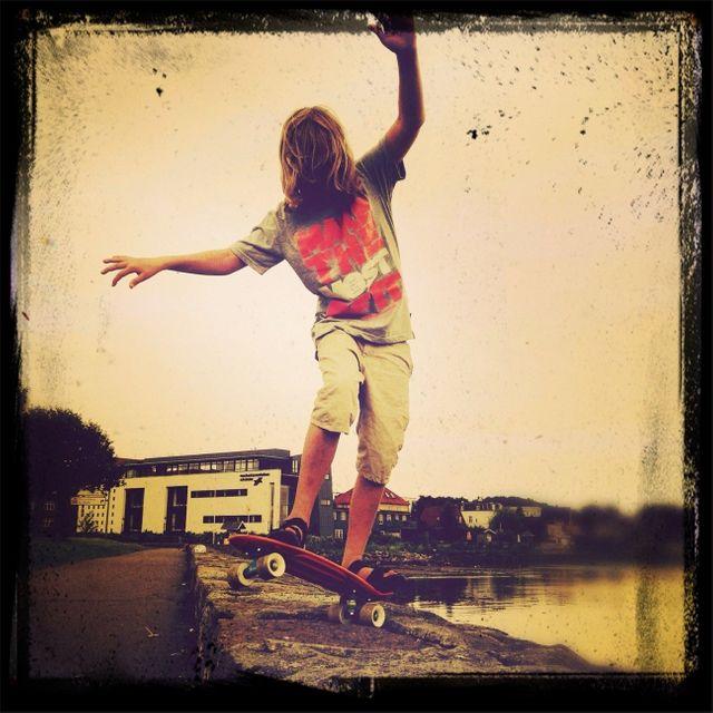Adolescent en skate sur un muret au bord de l'eau