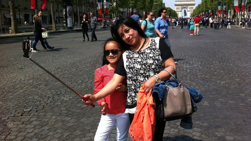 La perche à selfie de rigueur pour les piétons sur les Champs-Elysées