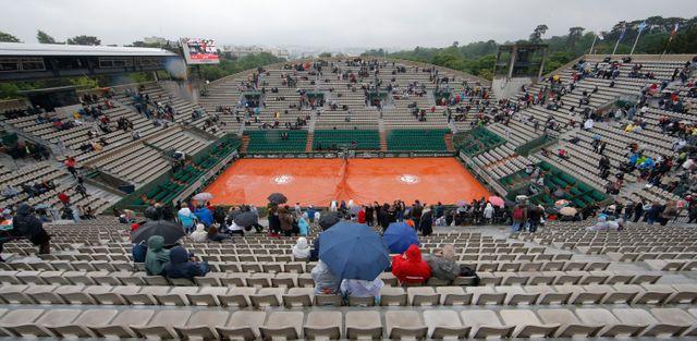 Roland Garros, 31 mai 2016. Les spectateurs se protègent de la pluie.