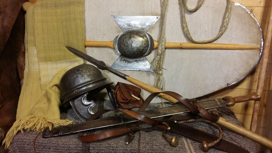 La panoplie d'un guerrier gaulois, lance, bouclier, épée longue, casque de fer, le torque (collier) et le sayon (manteau) de laine.