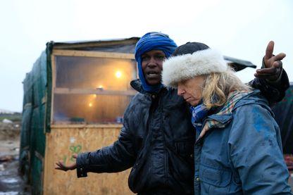 """Maya, une bénévole de """"Auberge des Migrants"""" écoute Muhammad, un migrant du Soudan qui vit dans la Jungle de Calais"""