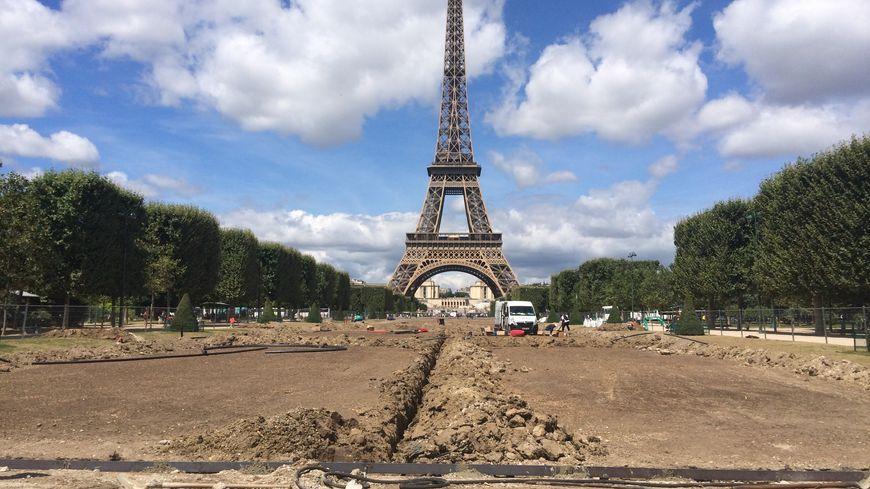 Pour remettre en état les pelouses centrales du Champ de Mars,  les ouvriers doivent creuser des tranchées.