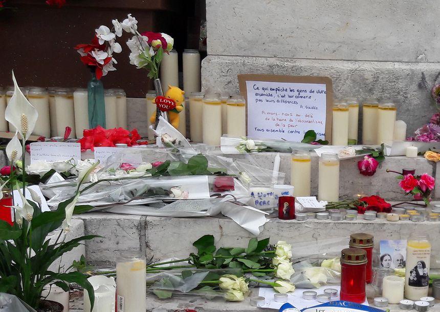 Devant l'hôtel de ville de Saint-Étienne-du-Rouvray, bougies, messages et fleurs.