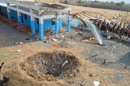 Des locaux observent les dommages d'un bombardement  dans la région de Hajja au Yemen, le 16 août 2016
