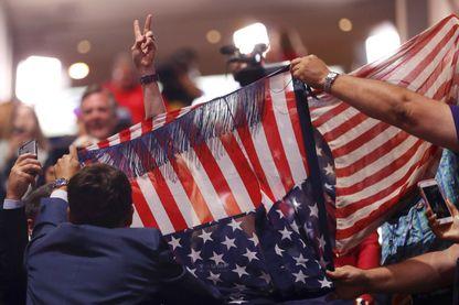 Des supporters de Donald Trump tentent de cacher une opposante du groupe Code Pink derrière un drapeau américain. Elle tient des bannières anti racisme et anti haine