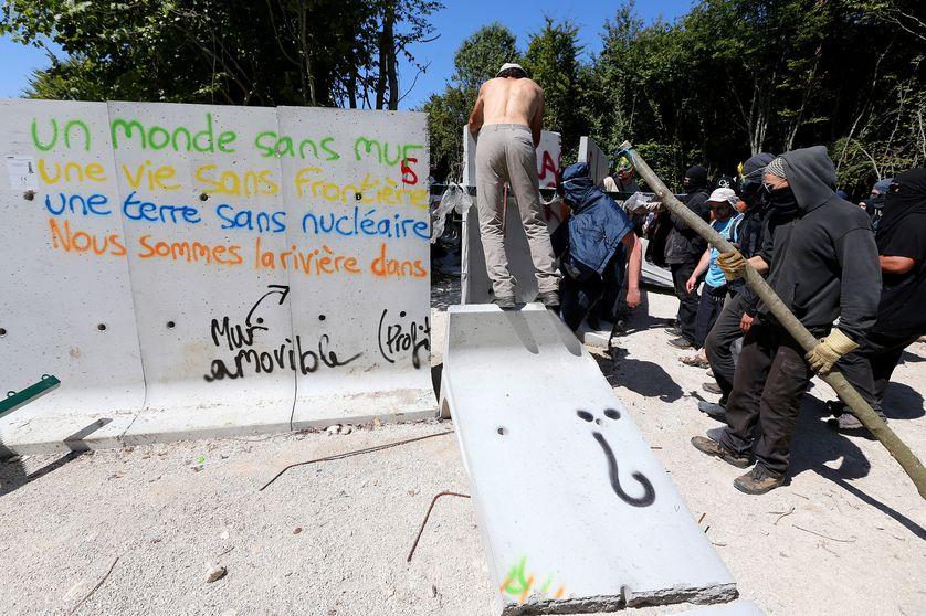 Des opposants au projet de stockage des déchets radioactifs de Bure (Meuse) détruisent un mur de protection du chantier, le 14 août 2016