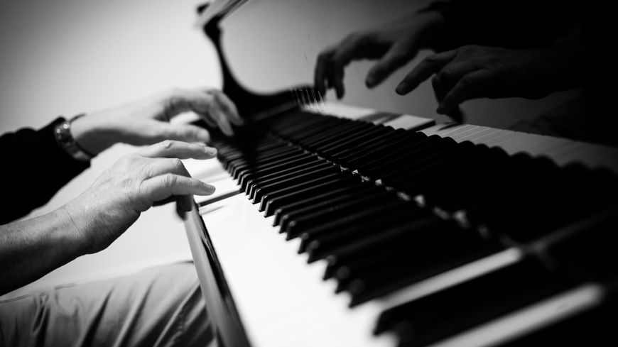 Des mains sur un piano.