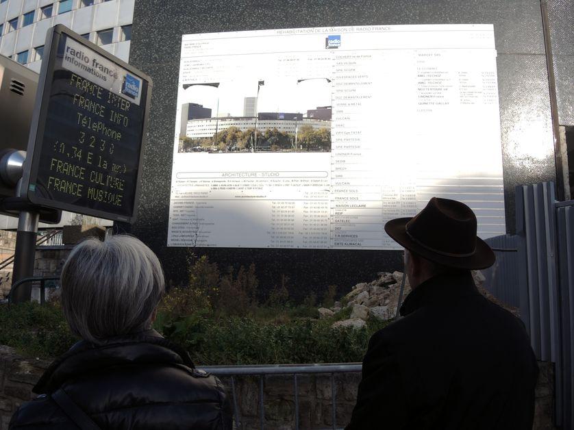 Bernard face au panneau décrivant la réhabilitation du bâtiment de la Maison de la Radio