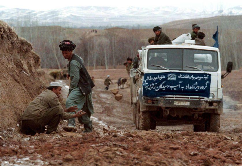 1998 : un convoi humanitaire tente d'avancer sur une chemin boueux, dans l'hiver afghan, après un tremblement de terre