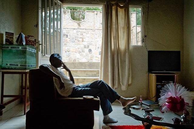 Tibagg, gay et activiste rwandais fume une cigarette dans le salon d'une amie dans un quartier de Kigali.
