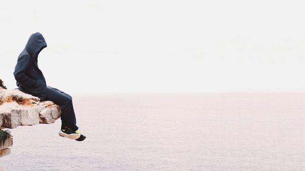 Homme assis au bord de la falaise