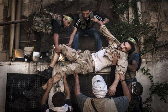 Alep, 20 août 2012. Un soldat blessé de l'Armée syrienne libre est porté à l'abri