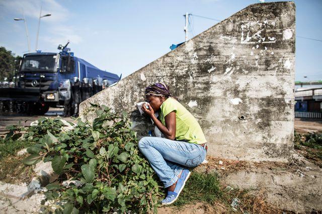 Une habitante de Librevillle se met à l'abri des affrontements derrière ce pan de mur