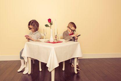 Un jeune garçon et une jeune fille préfèrent vraiment jouer avec leurs appareils mobiles que d'être avec l'autre.