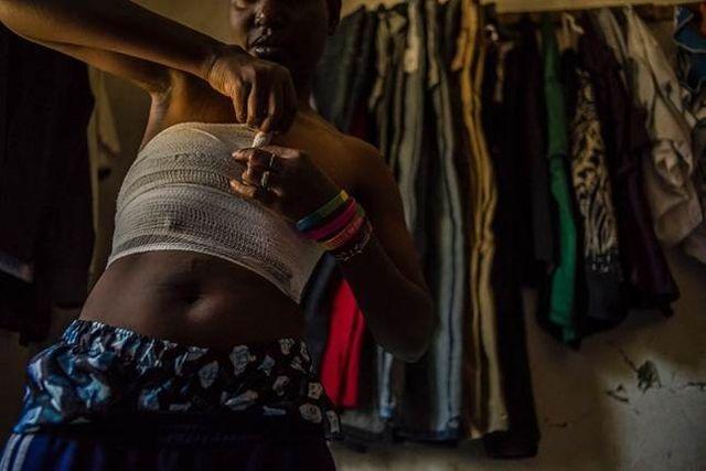 M., transgenre né femme, comprime sa poitrine au moyen d'une bande, pour avoir l'apparence d'un homme.