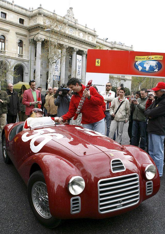 Andrea Costonovo, le directeur européen de Ferrari, reçoit un trophée d'un pilote assis à une Ferrari 125 S de 1948, sur la place Lealtad à Madrid le mercredi 4 avril 2007