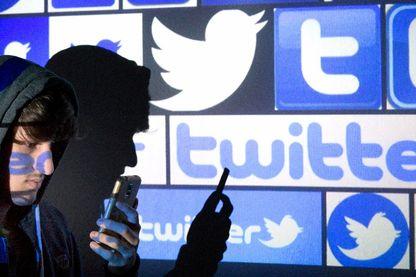 Un jeune homme devant le logo de Twitter
