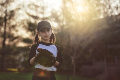 Une jeune fille s'apprête à lancer une balle de baseball