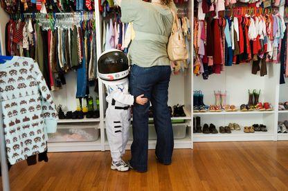 Enfant en costume de cosmonaute, accroché à la jambe de sa mère dans une boutique de vêtement