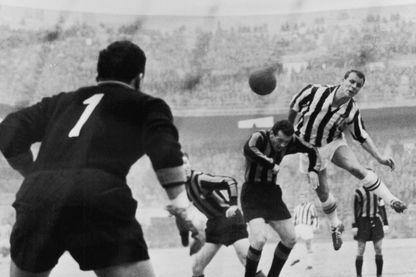 Le footballeur John Charles sautant au-dessus de deux joueurs de l'Inter de Milan afin de marquer pour la Juventus de Turin