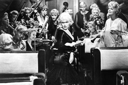 """Les acteurs Marilyn Monroe, Tony Curtis et Jack Lemmon avec pour chef d'orchestre Joan Shawlee (à droite) dans une scène du film 'Some Like It Hot' (""""Certains l'aiment chaud"""")"""