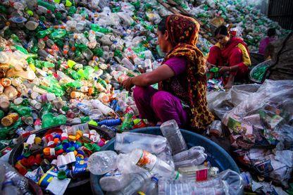 Des femmes travaillent pour recycler des produits en plastique, essentiellement des bouteilles en plastique, dans une usine locale du Bangladesh.