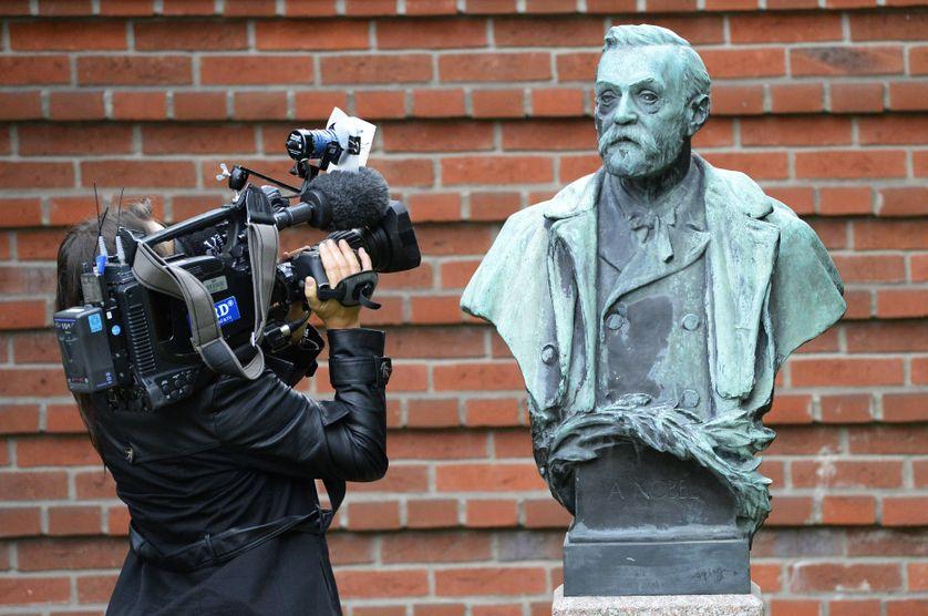 Une journaliste en train de filmer une statue du fondateur du prix Nobel, le Suédois Alfred Nobel, à Stockholm en octobre 2013.