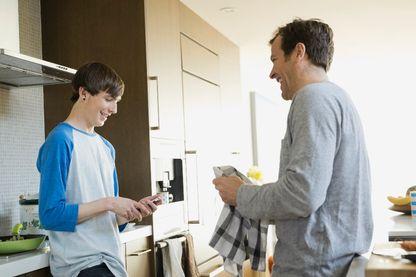 Un père et son fils discutent dans la cuisine familiale