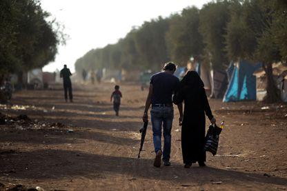 Un homme armé marche avec une femme à l'intérieur d'un camp de réfugiés déplacés dans la campagne au nord d'Alep, en Syrie, 10 octobre 2016.