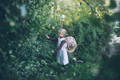 Un enfant en costume d'escargot fait maison caresse une feuille dans le jardin