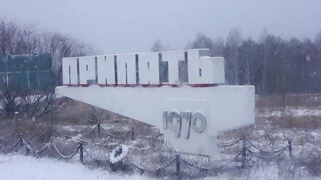 Panneau d'entrée Pripiat, ville créée en 1970 afin d'héberger les employés de la centrale nucléaire de Tchernobyl. Au pied, couronnes et bouquets.