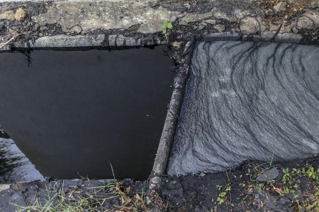 L'eau qui circule dans les gouttières est pollué à l'extérieur de l'usine Aditya Jeans Washers,  dans la zone industrielle Mundargi de Ballari, Karnataka, en Inde (mai 2016)