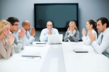 Groupes de personnes qui prient avant une réunion de travail.