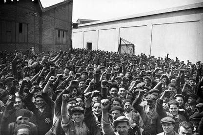 Des ouvriers grévistes qui occupent les usines Renault posent, poings levés, pour le photographe à l'intérieur de l'établissement à Boulogne-Billancourt au mois de mai 1936 lors des grandes grèves qui ont marqué le gouvernement du Front populaire en 1936.