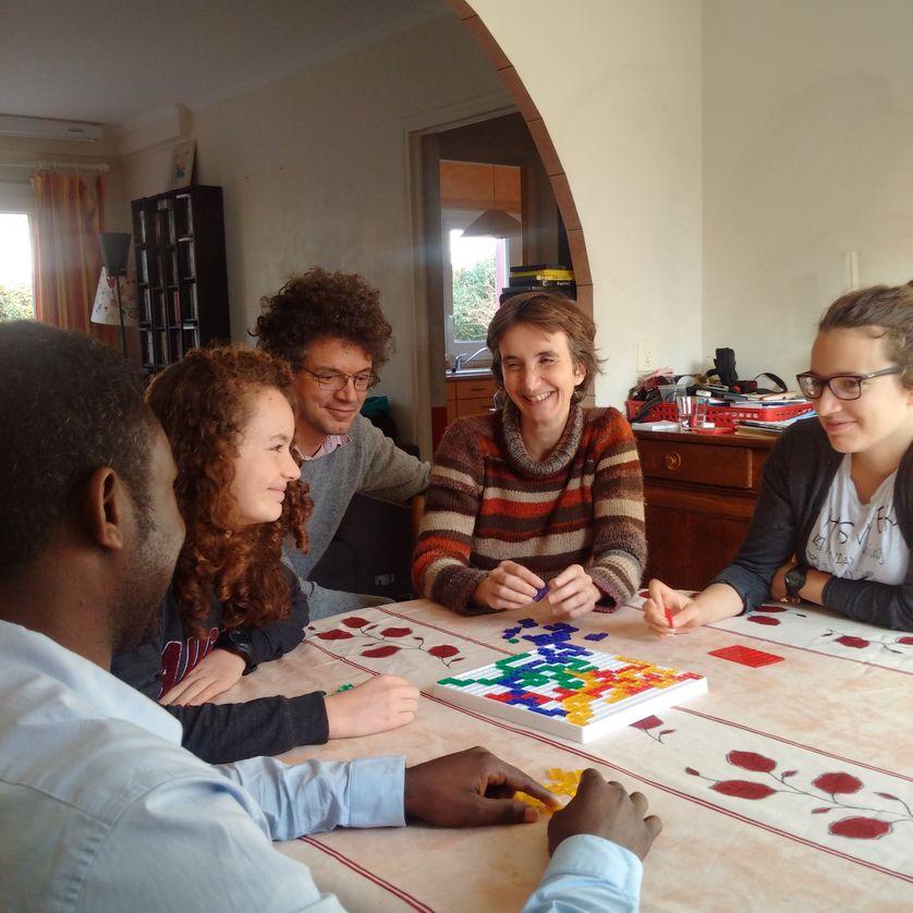De gauche à droite : Hadjo (27 ans, migrant soudanais), Solène (13 ans), Romain et Anne-Caroline (les parents accueillants) et Camille (16 ans) en train de jouer à Blokus.