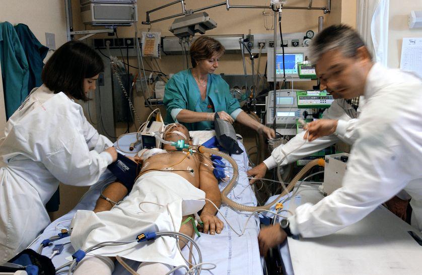 Un médecin assité d'une externe, d'une infirmière et d'un brancardier se préparent à transférer un malade dans le coma du service de réanimation vers la radiologie pour passer un scanner