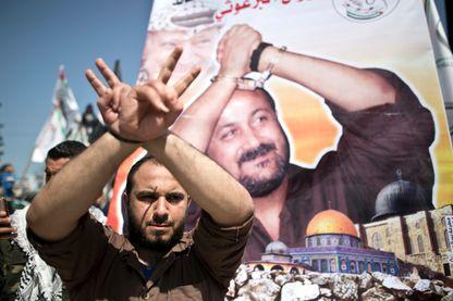 Palestinien devant une affiche portant le portrait du chef du Fatah emprisonné, Marwan Barghuti
