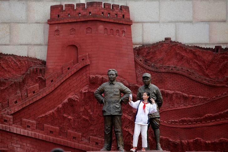 Une femme prenant un selfie avec des statues représentant l'ancien président Mao Zedong et et l'ancien général Zhu De pendant la guerre contre le Japon.