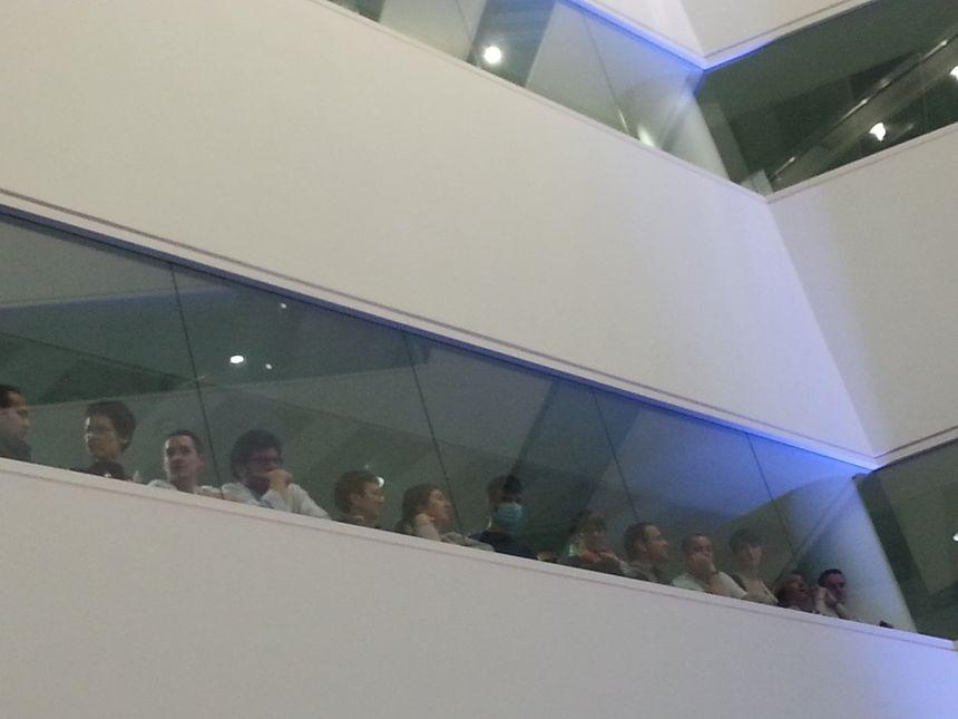 Derrière les vitres, les employés de l'hôpital attendent le Président.