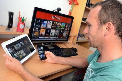 Un jeune homme regarde la plateforme de vidéos à la demande en streaming NETFLIX sur un écran d'ordinateur une tablette et un smartphone