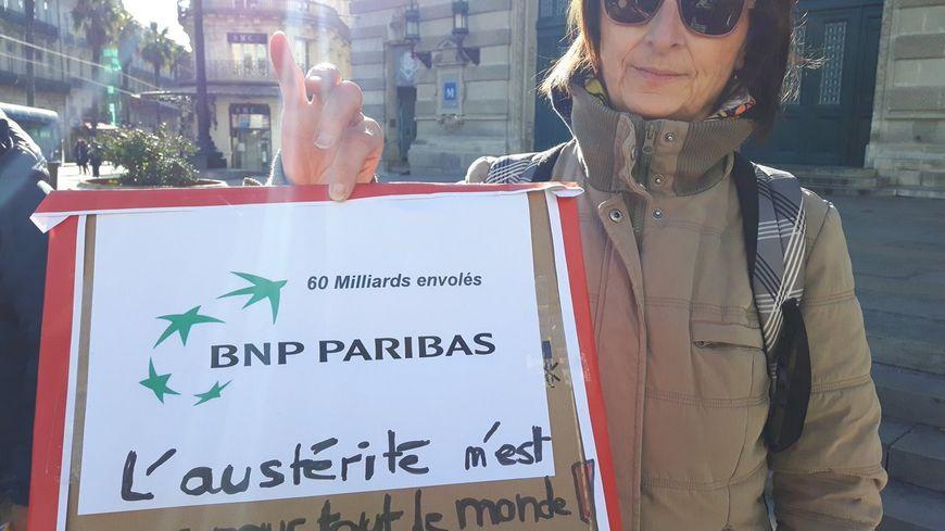 une militante d'Attac devant l'action symbolique à l'agence BNP Paribas Comédie Montpellier