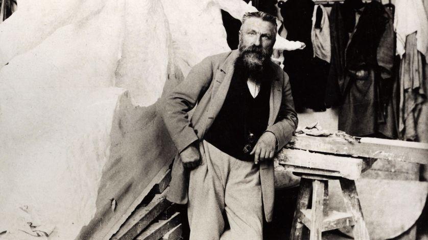 Photo d'Auguste Rodin dans son atelier à la fin des années 1890 avec la sculpture de Victor Hugo en arrière-plan.