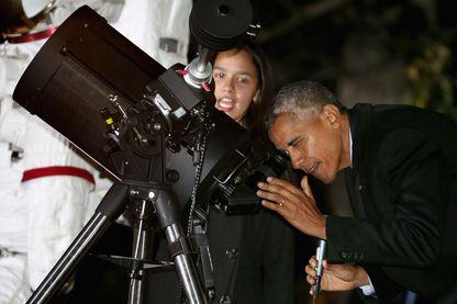 Barack Obama qui pour promouvoir la science regarde dans un téléscope