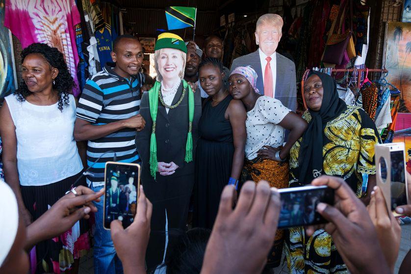 De jeunes tanzaniens posent en compagnie de photographies en grandeur nature des deux candidats à l'éléction présidentielle, lors d'un meeting organisé à l'ambassade américaine de Dar es Salaam, en Tanzanie il y a deux mois
